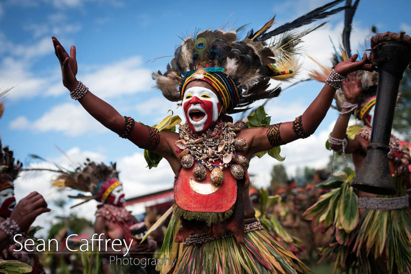 Tribal woman with red face paint and feather headdress playing drum at Goroka sing-sing (Tokua Culture Singsing Group)