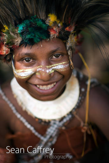 Tribal boy with paint and feather headdress at Goroka sing-sing