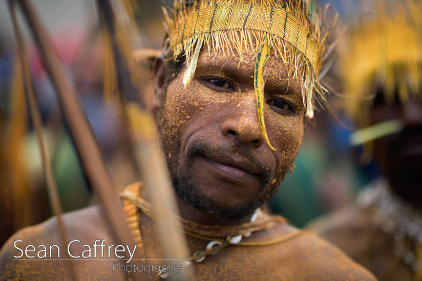 Tribal man with yellow face paint and feather headdress at Goroka sing-sing