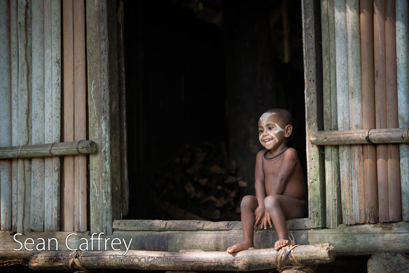 Little girl sitting in the doorway of a hut in Kundiman Village (Yokuim tribe)