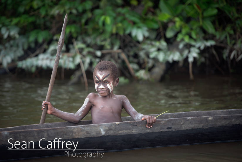 Young boy in canoe on Karawari River.