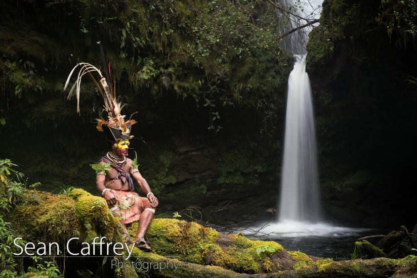 Huli wigmen wearing ceremonial wig in front of waterfall.